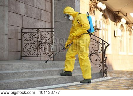 Person In Hazmat Suit Disinfecting Stairs With Sprayer Outdoors. Surface Treatment During Coronaviru