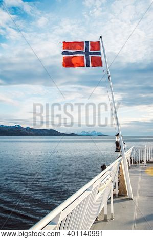 Norwegian Flag Hanging On The Railing Of The Ship And Waving Above The Water. Norvegian Fjord With A