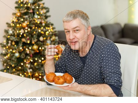 Caucasian Man Eating Olibol Near The Christmas Tree At Home, Portret, Oliebollen - Dutch Traditional