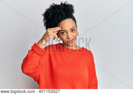 Young african american girl wearing casual clothes pointing unhappy to pimple on forehead, ugly infection of blackhead. acne and skin problem