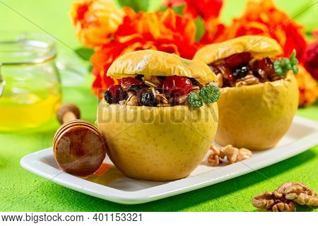 Baked Apples With Oatmeal, Walnuts, Dried Berries And Honey On A White Plate, Selective Focus. Conce