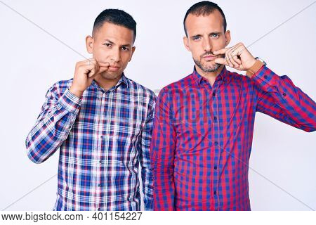 Young gay couple of two men wearing casual clothes mouth and lips shut as zip with fingers. secret and silent, taboo talking