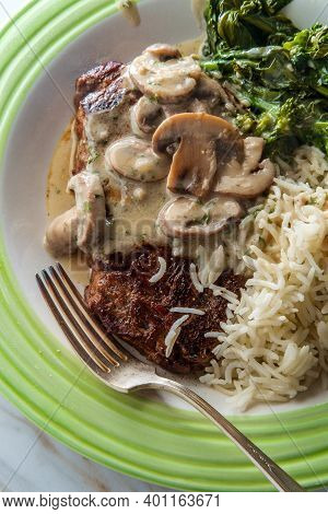 Grilled Club Steak With Creamy Marsala Wine Mushroom Sauce And Sides Of Rice And Broccoli Rabe
