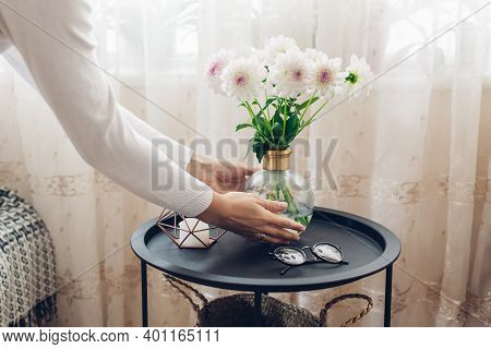 Woman Puts Vase With Flowers Dahlias In Vase On Table With Candle And Glasses. Taking Care Of Cozine