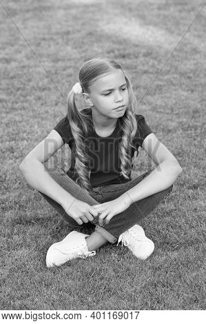 Why So Serious. Little Child Sit On Green Grass. Little Girl Wear Long Hairstyle. Little Kid In Summ