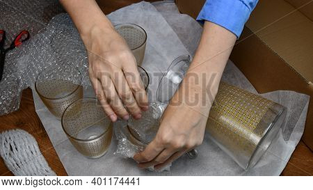 Woman Hands Pack Up Breakable Fragile Glassware Into Wrapping Bubble Plastic And Put Into Cardboard