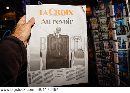 Strasbourg, France - Dec 4, 2020: Pov Male Hand Holding Au Revoir Goodbye Text On La Croix Newspaper