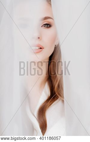 Portrait Of A Beautiful Young Woman In A White Robe Under A Wedding Veil.