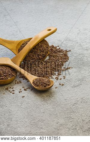 Flax Seeds In Three Wooden Spoons On A Concrete Background, A Dietary Product That Reduces Cholester