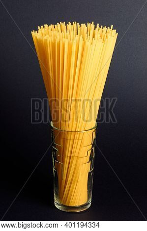 Spaghetti In A Glass On A Black Background, Italian Cuisine And Cooking.
