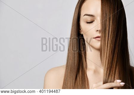 Portrait Of Sensual Young Slim Woman With Closed Eyes Holding Strand Of Her Long Silky Hair Covering