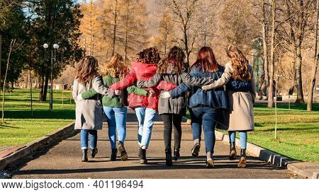 Young Group Of Girls Walking In Autumn Park, Autumn Clothes And Autumn Walk. Graduation From High Sc