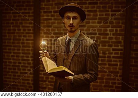 Portrait of a detective man standing with a magnifying glass and his notebook. Retro style. Occupation, criminal world.