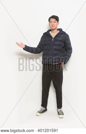 full length handsome casual man sweater and black jacket ,black jeans,and sneakers ,welcome gesture.  Posing in studio