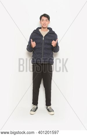 full length handsome casual man sweater and black jacket ,black jeans,and sneakers posing and happy. Cheerful expression and winner gesture.