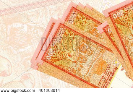 100 Sri Lankan Rupees Bills Lies In Stack On Background Of Big Semi-transparent Banknote. Abstract P