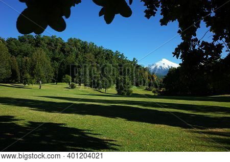 Nature of Chile. Beautiful landscape, sun and shadow, Green grass and forest on hill, Snowy cone of Villarrica volcano under blue sky in sunny day. Green environment, Pucon