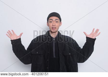 Portrait of young man wearing in black jacket with black hat and raised up arms