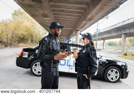 Multicultural Police Officers With Paper Cups Talking Near Patrol Car On Blurred Background On Urban
