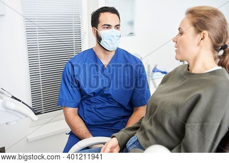 Portrait View Of The Male Dentist In Dental Office Talking With Female Patient