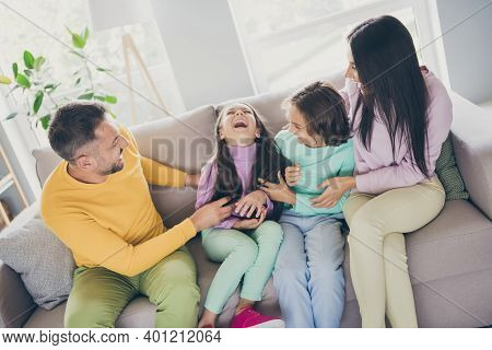 Photo Of Full Big Family Four Members Sit Couch Daddy Tickle Daughter Wear Colorful Sweater Pants In