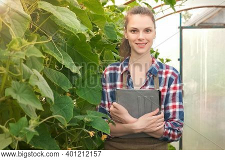 Agronomist Woman With Tablet Working In Greenhouse With Cucumbers And Looking At Camera And Smiling.
