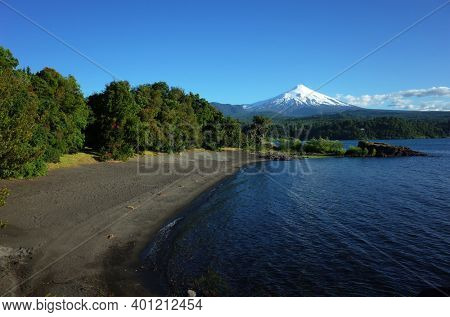 Nature of Chile, Beautiful landscape, Dark volcanic sand beach on Villarrica lake, snow capped Villarrica volcano under blue sky in sunny day. Green environment, Pucon