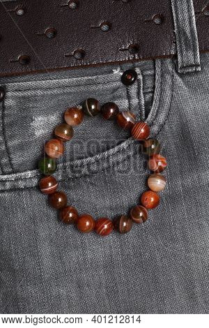 Bracelet Made Of Agate Stones On The Hand Close-up On The Background Of Jeans. Bracelet On The Hand