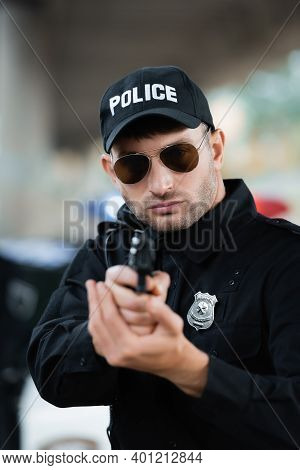 Police Officer In Uniform And Sunglasses Holding Gun On Blurred Foreground Outdoors.