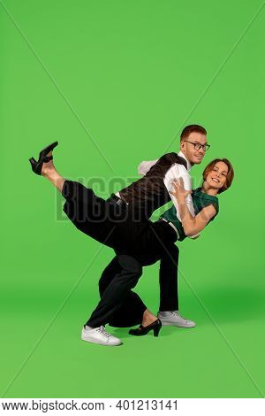 Fun. Old-school Fashioned Young Woman Dancing Isolated On Green Studio Background. Artist Fashion, M
