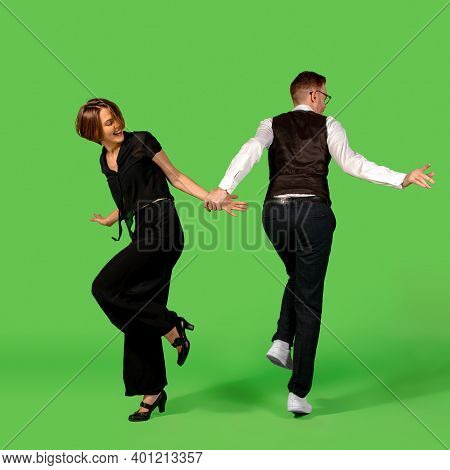 Rock N Roll. Old-school Fashioned Young Woman Dancing Isolated On Green Studio Background. Artist Fa