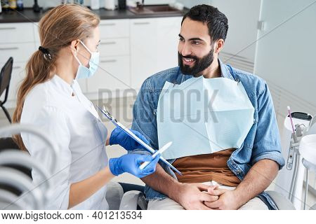 Dentist Showing The Paper To A Smiling Man Client
