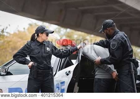 Multicultural Police Officers Arresting Hooded Offender Near Colleague And Patrol Car On Urban Stree