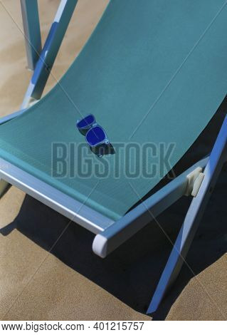 Turquoise Sun Lounger, Chaise Longue Textile Chair Close Up With Blue Sunglasses On Sand, Vacation,