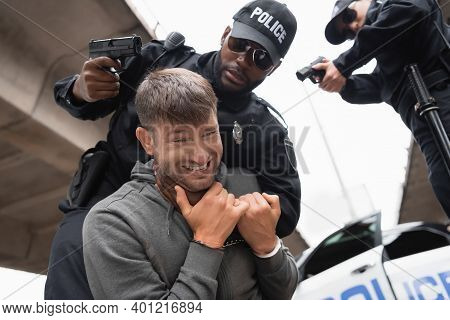 Low Angle View Of African American Policeman Choking Offender While Aiming With Pistol Near Colleagu