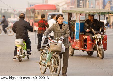 Suzhou, Jiangsu Province, China, Asia - November 24, 2008: Woman With Bicycle Crossing The Street In