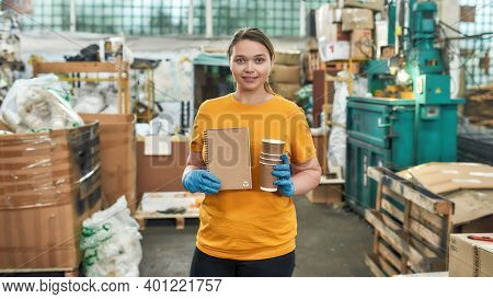 Young Caucasian Girl Holding Paper Notepad Made From Coffee Cups While Standing Inside Waste Station