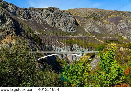 The river with bright green water. River and old bridge Kawarau between Queenstown and Cromwell. Incredible Adventures in New Zealand. The concept of extreme, active and photo tourism