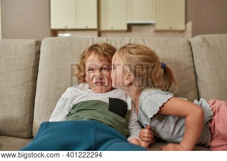 Portrait Of Little Boy Looking Disgruntled While His Sibling Sister Kissing Him On Cheek, Cuddling T