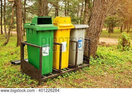 Trash Bin Located In The Public Park. Three Containers Of Different Colors For Collecting Different