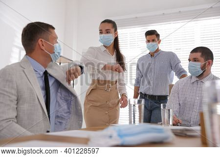 Coworkers With Protective Masks Making Elbow Bump In Office. Informal Greeting During Covid-19 Pande