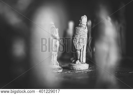 A Black And White Portrait Of A White Stone Soldier On A Stone Chessboard Facing A Black Soldier And