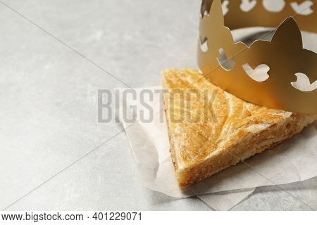 Slice Of Traditional Galette Des Rois With Paper Crown On Light Grey Table. Space For Text