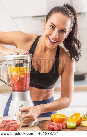 Fit Girl Makes Fitness Food By Blending Citrus Fruit Into A Smoothie.