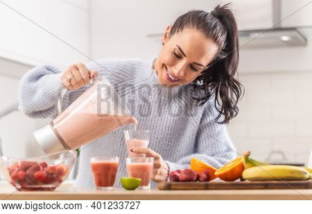 Woman Pours Fruit Smoothie Into Cups In A Kitchen.
