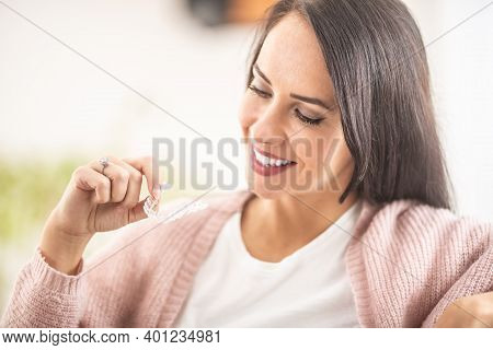Smiling Woman Holds Invisible Braces In Her Hand.