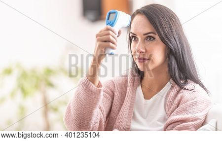 Woman Self-measuring Temperature With An Infrared Digital Thermometer On Her Forehead.