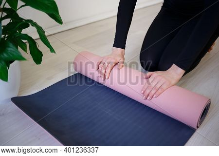 Young Woman Unfolds Yoga Mat Before Practice.