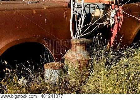 A Rusty And Junky  Scene Of Old Pail, Milk Can And Body Of A Car.