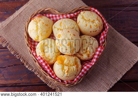 Homemade Cheese Bread, Traditional Brazilian Snack, In A Heart-shaped Basket On A Rustic Kitchen Tab